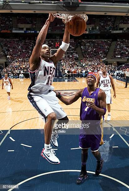 Vince Carter of the New Jersey Nets dunks over Lamar Odom of the Los Angeles Lakers on February 9 2005 at the Continental Airlines Arena in East...