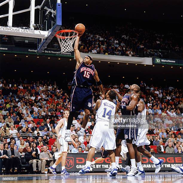 Vince Carter of the New Jersey Nets dunks past Jameer Nelson of the Orlando Magic at TD Waterhouse Centre on December 21 2005 in Orlando Florida The...