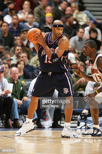 Vince Carter of the New Jersey Nets is defended by Jason Richardson of the Golden State Warriors at the Arena in Oakland on November 21 2005 in...