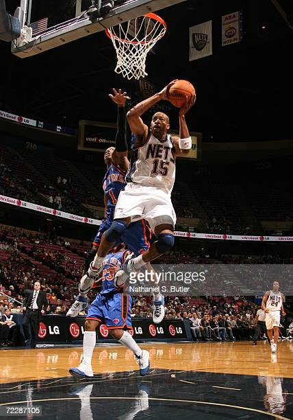 Vince Carter of the New York Knicks dunks against Steve Francis of the New Jersey Nets on October 27 2006 at the Continental Airlines Arena in East...
