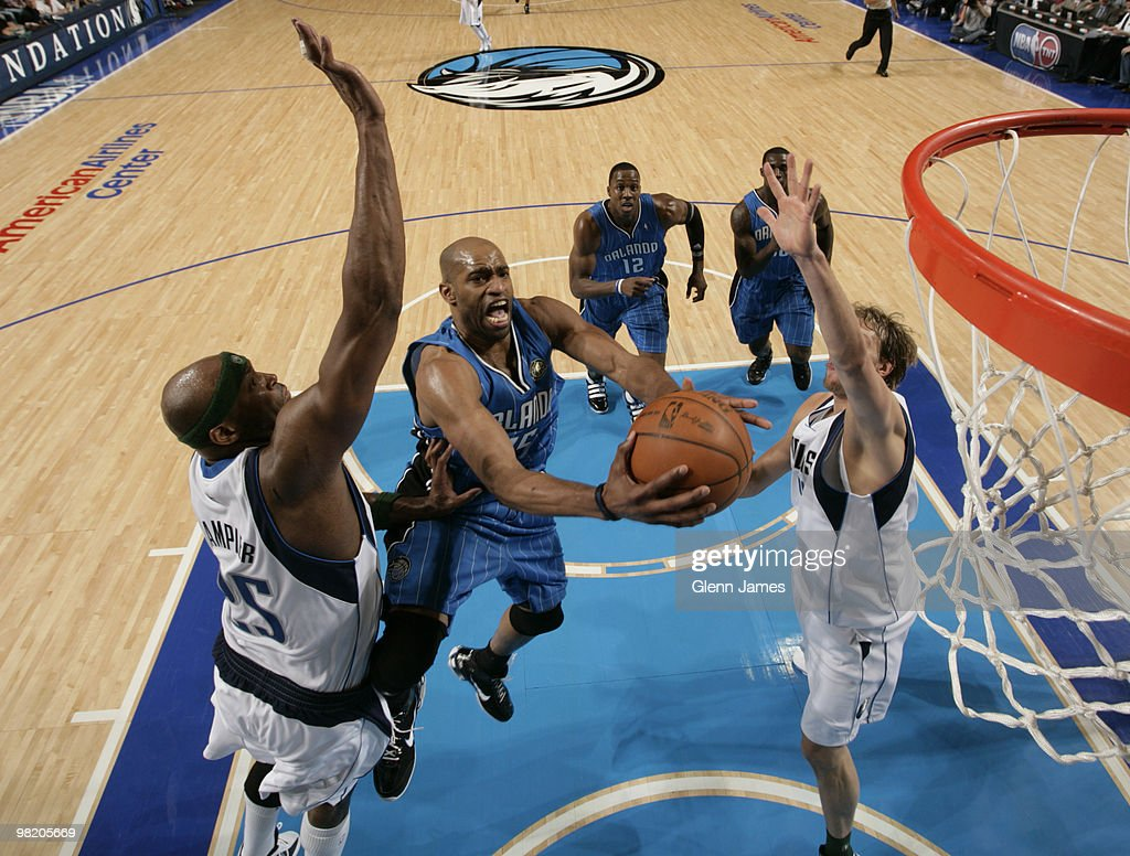 Vince Carter #15 of the Orlando Magic goes in for the layup against Erick Dampier #25 and Dirk Nowitzki #41 of the Dallas Mavericks during a game at the American Airlines Center on April 1, 2010 in Dallas, Texas.