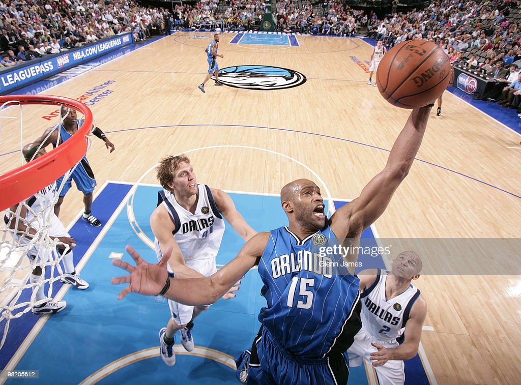 Vince Carter #15 of the Orlando Magic skies for the rebound against Jason Kidd #2 and Dirk Nowitzki #41 of the Dallas Mavericks during a game at the American Airlines Center on April 1, 2010 in Dallas, Texas.