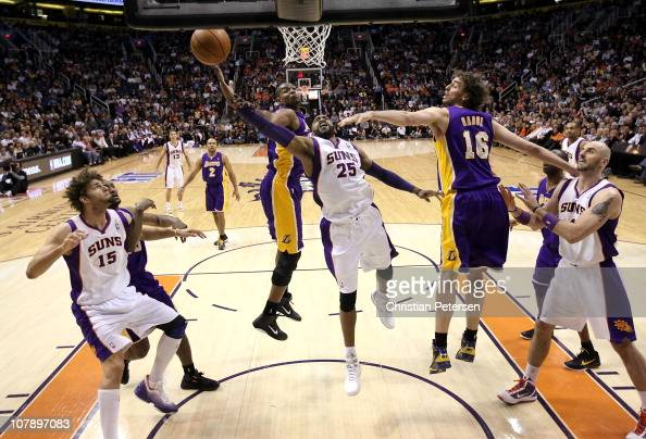 Vince Carter of the Phoenix Suns lays up a shot past Andrew Bynum and Pau Gasol of the Los Angeles Lakers during the NBA game at US Airways Center on...
