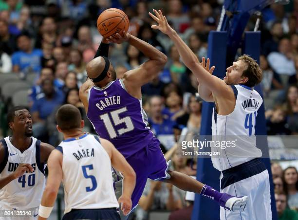 Vince Carter of the Sacramento Kings drives to the basket against Harrison Barnes of the Dallas Mavericks JJ Barea of the Dallas Mavericks and Dirk...