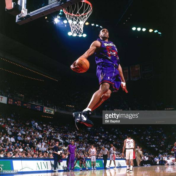 Vince Carter of the Toronto Raptors elevates for a spectacular slam dunk against the Houston Rockets during a 1999 NBA game at the Summit in Houston...