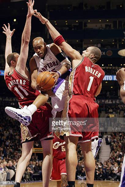 Vince Carter of the Toronto Raptors jumps between the arms of Zydrunas Ilgauskas and Carlos Boozer of the Cleveland Cavaliers during the game at the...
