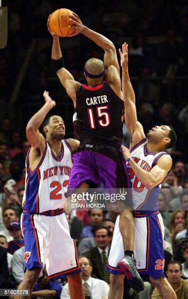 Vince Carter of the Toronto Raptors shoots over Marcus Camby and Allan Houston of the New York Knicks in second quarter action of their Eastern...