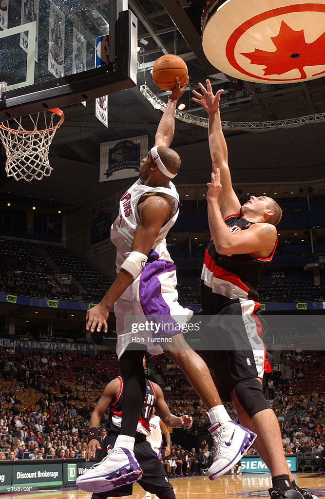 Vince Carter of the Toronto Raptors soars along the baseline ahead of Joel Przybilla of the Portland Trailblazers on October 21 2004 at the Air...