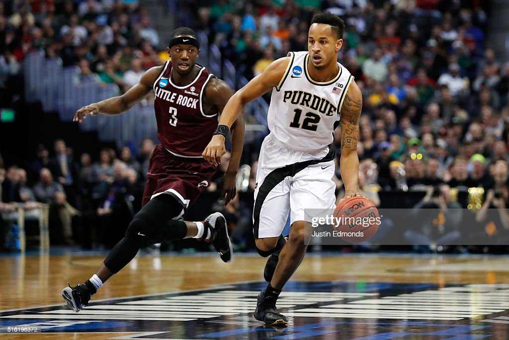 Vince Edwards of the Purdue Boilermakers drives the ball past Josh Hagins of the Arkansas Little Rock Trojans during the first round of the 2016 NCAA...