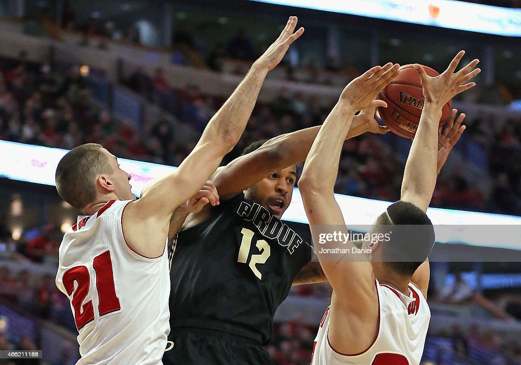 Vince Edwards #12 of the Purdue Boilermakers gets off a pass under pressure from <a gi-track='captionPersonalityLinkClicked' href=/galleries/search?phrase=Josh+Gasser&family=editorial&specificpeople=7355332 ng-click='$event.stopPropagation()'>Josh Gasser</a> #21 and <a gi-track='captionPersonalityLinkClicked' href=/galleries/search?phrase=Bronson+Koenig&family=editorial&specificpeople=9510843 ng-click='$event.stopPropagation()'>Bronson Koenig</a> #24 of the Wisconsin Badgers during the semifinal round of the 2015 Big Ten Men's Basketball Tournament at the United Center on March 14, 2015 in Chicago, Illinois.