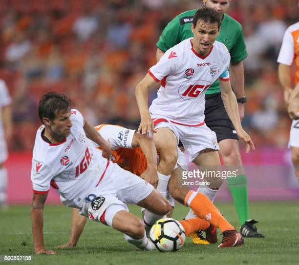 Vince Lia and Isaias of Adelaide both scramble for the ball during the round two ALeague match between the Brisbane Roar and Adelaide United at...