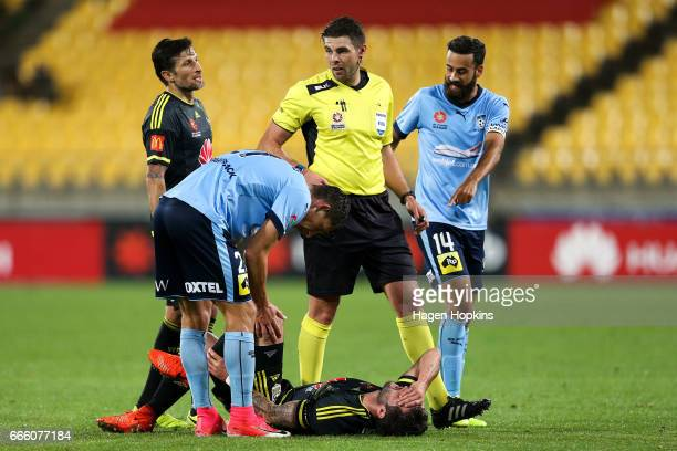 Vince Lia of the Phoenix and Alex Brosque of Sydney FC talk to referee Shaun Evans while Tom Doyle of the Phoenix recovers from a tackle during the...