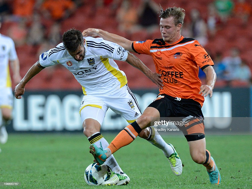 Vince Lia of the Phoenix is pressured by the defence of Nick Fitzgerald of the Roar during the round 14 A-League match between the Brisbane Roar and the Wellington Phoenix at Suncorp Stadium on January 1, 2013 in Brisbane, Australia.