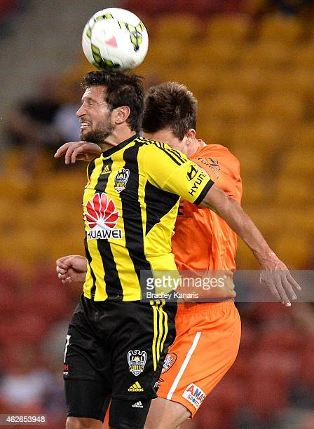 Vince Lia of Wellington Phoenix and James Donachie of the Roar compete for the ball during the round 16 ALeague match between the Brisbane Roar and...