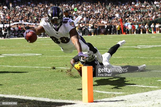 Vince Mayle of the Baltimore Ravens dives for a touchdown against the Oakland Raiders during their NFL game at OaklandAlameda County Coliseum on...