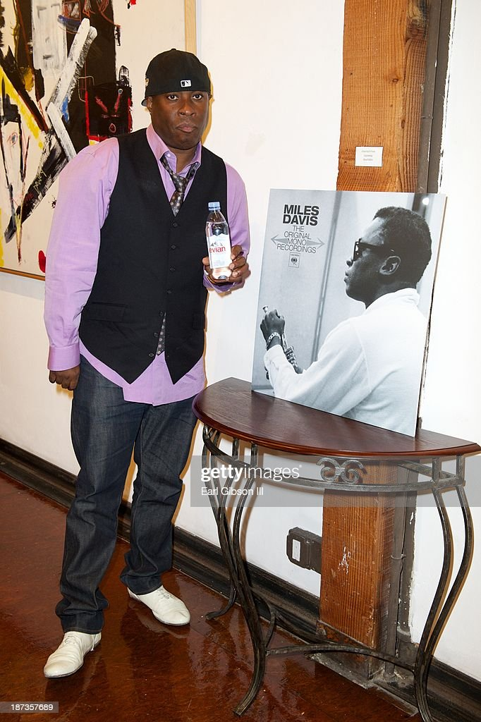Vince Wilburn Jr. poses with a photo of his uncle Miles Davis at the 'Miles Davis: The Collected Artwork' Launch Party at Mr. Musichead Gallery on November 7, 2013 in Los Angeles, California.
