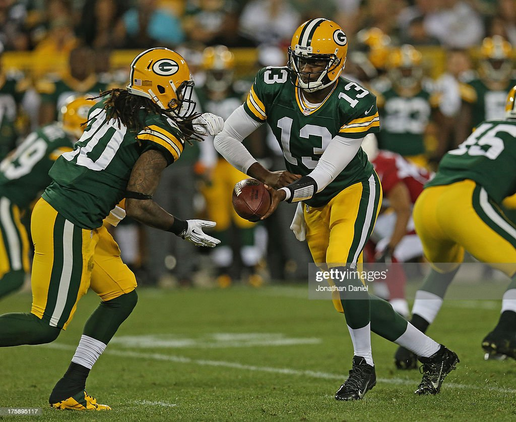 <a gi-track='captionPersonalityLinkClicked' href=/galleries/search?phrase=Vince+Young&family=editorial&specificpeople=179485 ng-click='$event.stopPropagation()'>Vince Young</a> #13 of the Green Bay Packers hands off to <a gi-track='captionPersonalityLinkClicked' href=/galleries/search?phrase=Alex+Green&family=editorial&specificpeople=6683075 ng-click='$event.stopPropagation()'>Alex Green</a> #20 against the Arizona Cardinals at Lambeau Field on August 9, 2013 in Green Bay, Wisconsin.