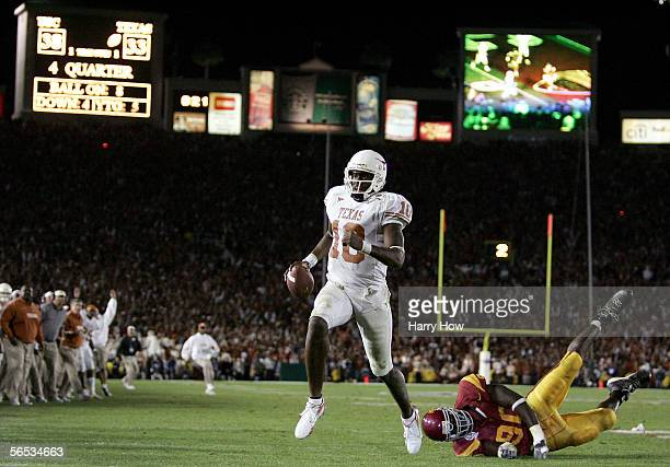 Vince Young of the Texas Longhorns runs past Frostee Rucker of the USC Trojans to score a touchdown and put the Longhorns up by one in the final...