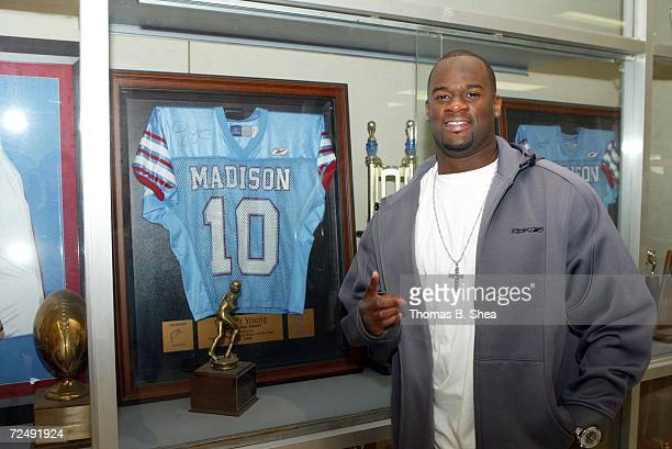 Vince Young poses for a photo in front of his Madison High School football jersey during his visit to Madison High School on October 20 2006 in...