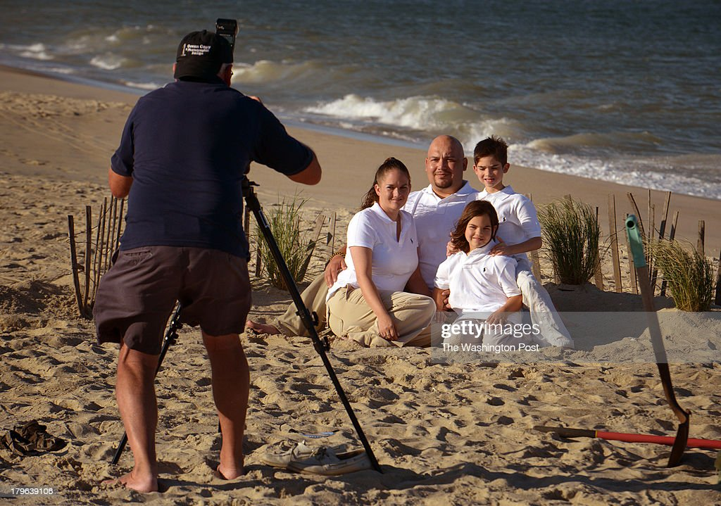 Vincent Aguilar and his family sit for a formal portrait by the seas. Residents and merchants have opened their resort homes to families of wounded warriors on September, 04, 2013 in Bethany Beach, DE. Vincents' daughter is Savannah, son is named Christian and wife is Nicole. They have driven here from Georgia.