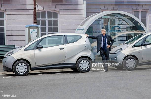 Vincent Bollore billionaire and chairman of the Bollore Group poses for a photo with an Autolib' electric Bluecar at the Autolib' carsharing...