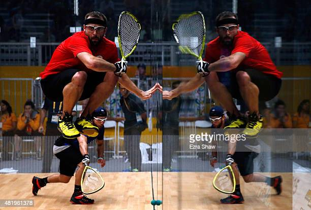 Vincent Gagnon of Canada jumps out of the way as Jose Rojas of the United States hits the ball during the men's team racquetball semifinal match on...