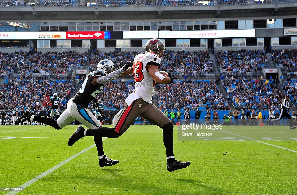 Vincent Jackson of the Tampa Bay Buccaneers runs a catch along the sideline as Drayton Florence of the Carolina Panthers defends during play at Bank...