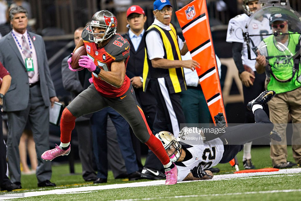 Vincent Jackson of the Tampa Bay Buccaneers runs down the sidelines and avoids the tackle of Kenny Vaccaro of the New Orleans Saints at MercedesBenz...