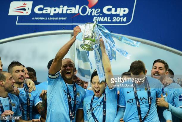 Vincent Kompany and Samir Nasri of Manchester City lift the trophy with team mates after the Capital One Cup Final between Manchester City and...