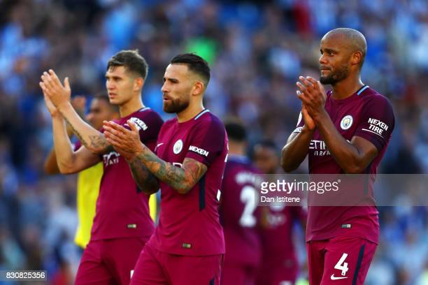 Vincent Kompany Nicolas Otamendi and John Stones of Manchester City applaud the fans after the Premier League match between Brighton and Hove Albion...