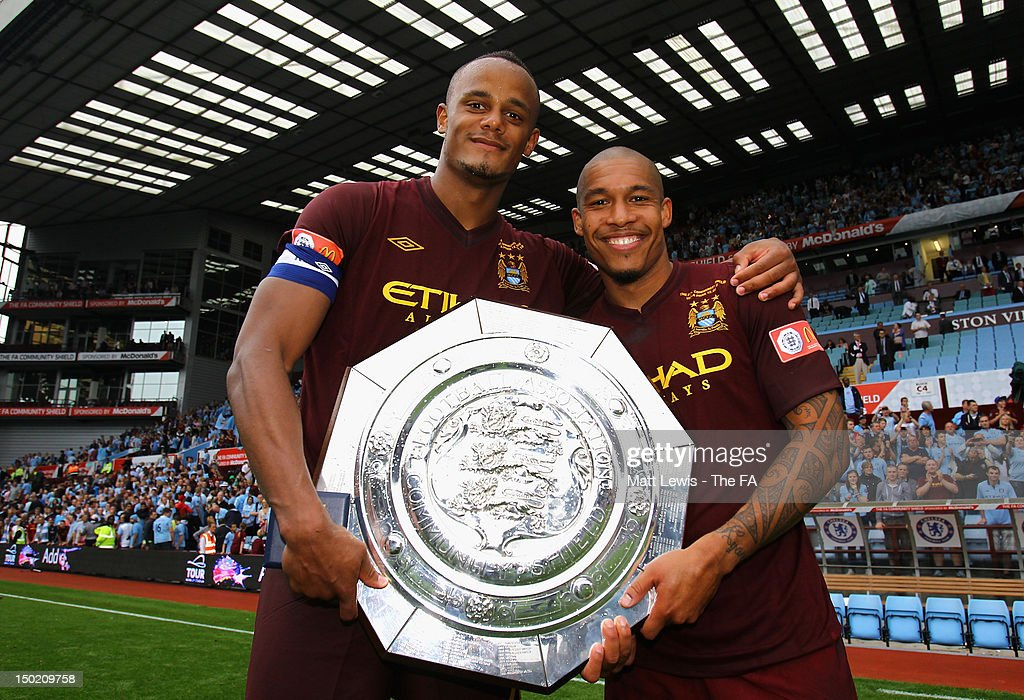 Vincent Kompany of Manchester City and team mate Nigel de Jong celebrate with the trophy after their team's victory at the end of the FA Community...