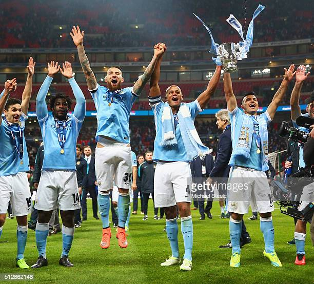 Vincent Kompany of Manchester City and team mates Jesus Navas Wilfred Bony Nicolas Otamendi and Sergio Aguero celebrate victory with the trophy after...