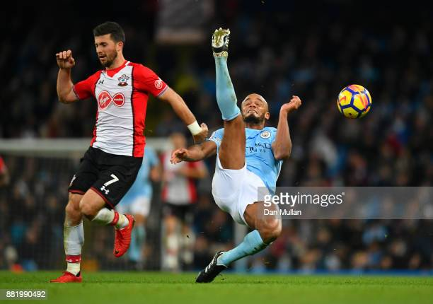 Vincent Kompany of Manchester City clears the ball while under pressure from Shane Long of Southampton during the Premier League match between...
