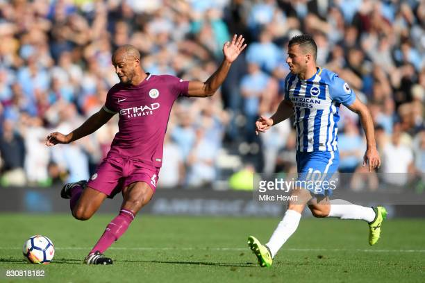 Vincent Kompany of Manchester City is challenged by Tomer Hemed of Brighton during the Premier League match between Brighton and Hove Albion and...