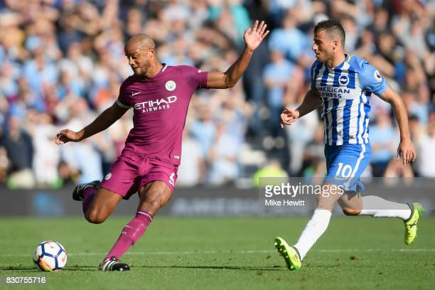 Vincent Kompany of Manchester City is put under pressure from Tomer Hemed of Brighton and Hove Albion during the Premier League match between...