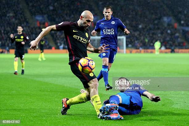 Vincent Kompany of Manchester City is tackled by Christian Fuchs of Leicester City during the Premier League match between Leicester City and...