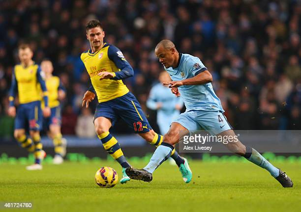 Vincent Kompany of Manchester City is watched by Olivier Giroud of Arsenal during the Barclays Premier League match between Manchester City and...