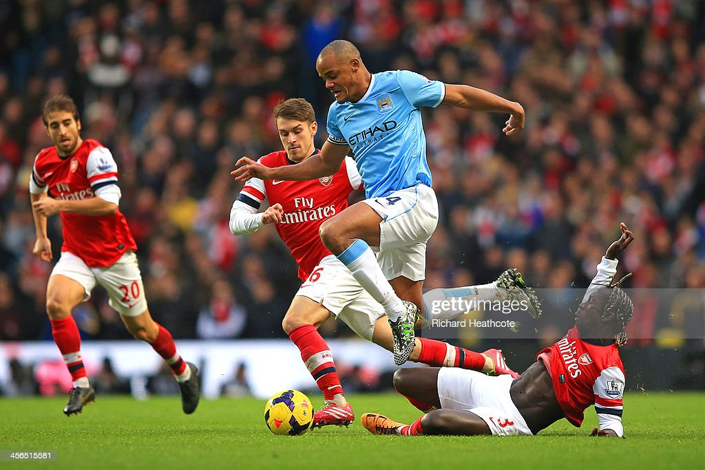 <a gi-track='captionPersonalityLinkClicked' href=/galleries/search?phrase=Vincent+Kompany&family=editorial&specificpeople=504694 ng-click='$event.stopPropagation()'>Vincent Kompany</a> of Manchester City leaps over a tackle from Bacary Sagna of Arsenal during the Barclays Premier League match between Manchester City and Arsenal at Etihad Stadium on December 14, 2013 in Manchester, England.