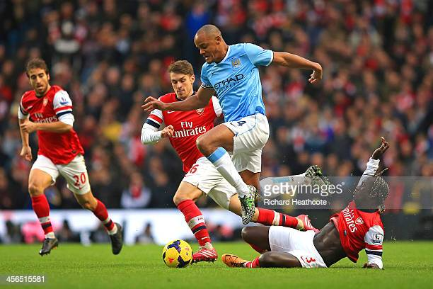 Vincent Kompany of Manchester City leaps over a tackle from Bacary Sagna of Arsenal during the Barclays Premier League match between Manchester City...