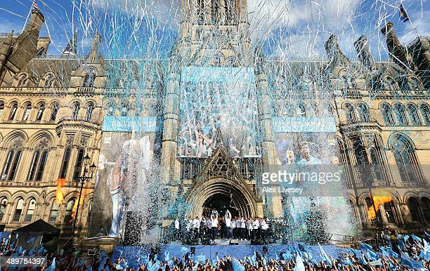 Vincent Kompany of Manchester City lifts the Barclays Premier League trophy aloft outside Manchester Town Hall at the start of the Manchester City...