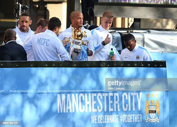 Vincent Kompany of Manchester City lifts the Barclays Premier League trophy aloft outside Manchester Town Hall as Joe Hart gives the thumbs up at the...