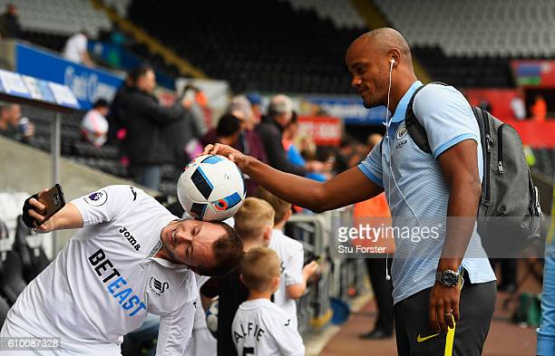 Vincent Kompany of Manchester City poses for a photo with a Swansea City fan prior to kick off during the Premier League match between Swansea City...