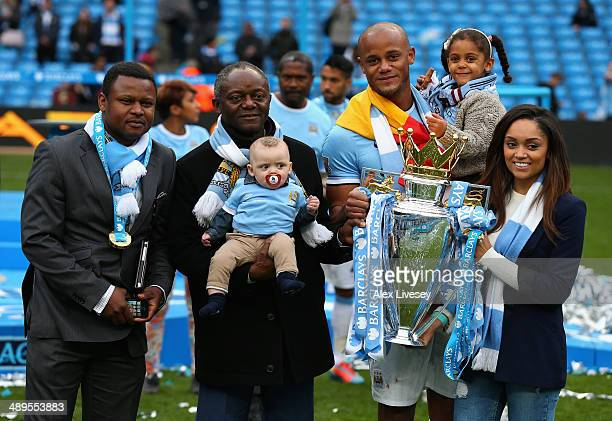 Vincent Kompany of Manchester City poses with the Premier League trophy and his family at the end of the Barclays Premier League match between...