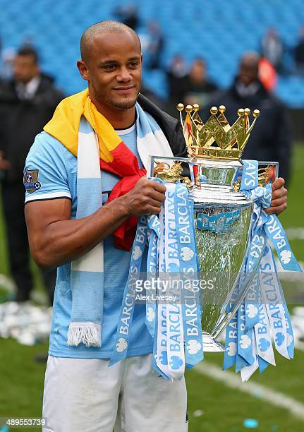 Vincent Kompany of Manchester City poses with the Premier League trophy at the end of the Barclays Premier League match between Manchester City and...