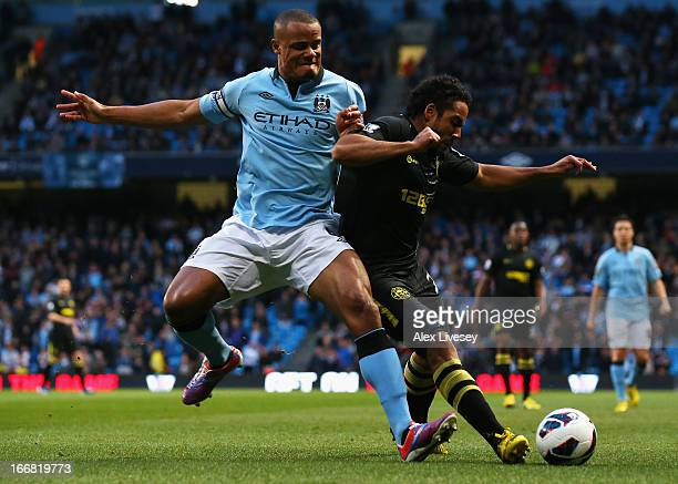 Vincent Kompany of Manchester City tangles with Jean Beausejour of Wigan Athletic during the Barclays Premier League match between Manchester City...