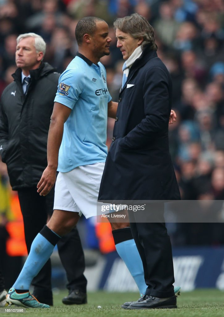 Vincent Kompany of Manchester City walks past Manager Roberto Mancini after being substituted during the Barclays Premier League match between Manchester City and Newcastle United at the Etihad Stadium on March 30, 2013 in Manchester, England.