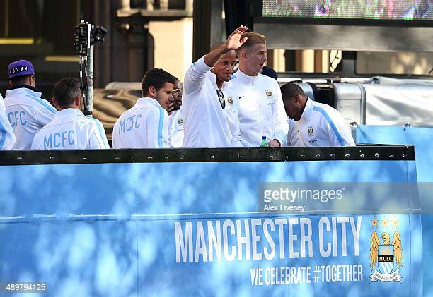 Vincent Kompany of Manchester City waves to the crowd outside Manchester Town Hall at the start of the Manchester City victory parade around the...
