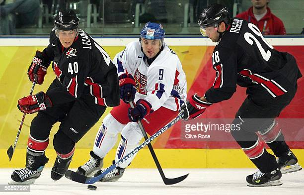 Vincent Lecavalier and Robyn Regehr of Canada and David Vyborny of the Czech Republic fight for control of the puck during the men's ice hockey...