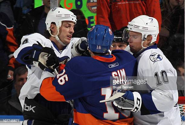 Vincent Lecavalier and Sean Bergenheim of the Tampa Bay Lightning confront Jon Sim at the Nassau Coliseum on December 22 2010 in Uniondale New York...