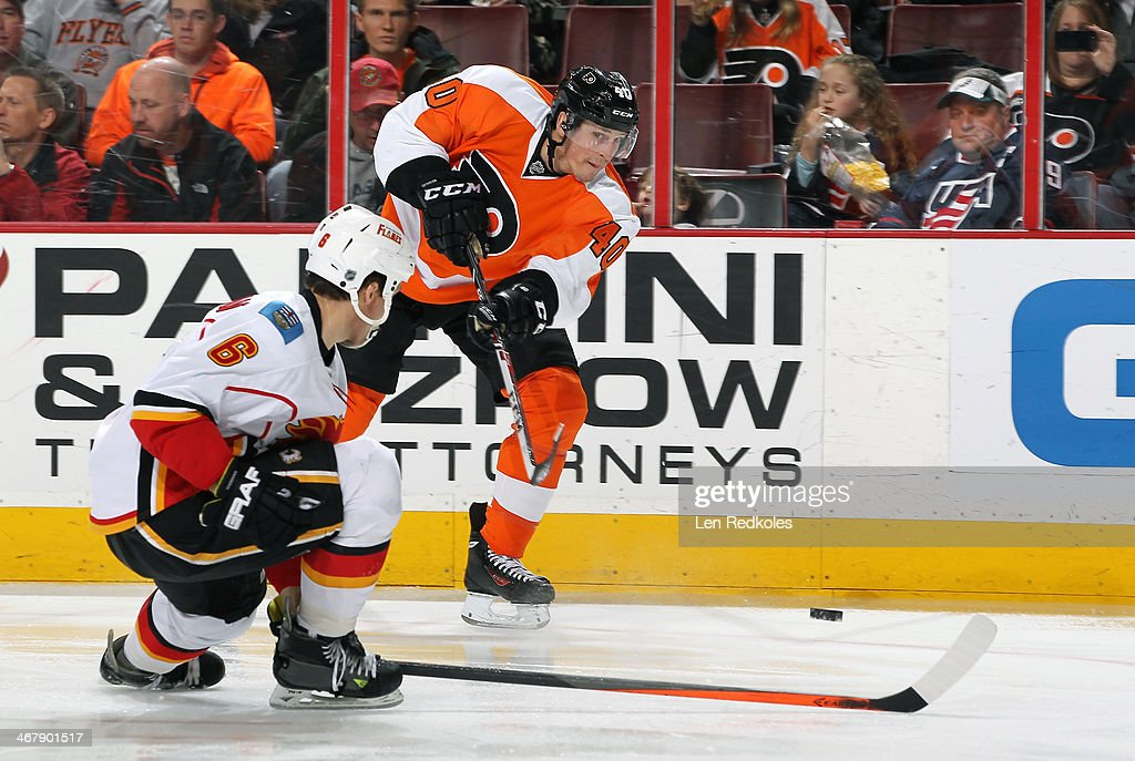 Vincent Lecavalier #40 of the Philadelphia Flyers shoots the puck just over the stick of Dennis Wideman #6 of the Calgary Flames on February 8, 2014 at the Wells Fargo Center in Philadelphia, Pennsylvania.